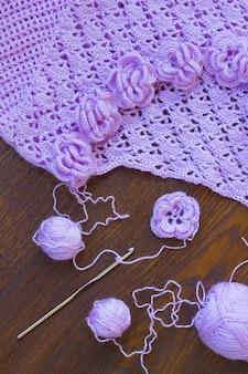 Gomitolo di filato viola, gancio e giacca lavorata a maglia sul tavolo