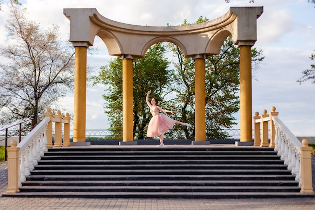 Una ballerina balla con la gamba sollevata in un arco di colonne nell'architettura urbana sull'argine...