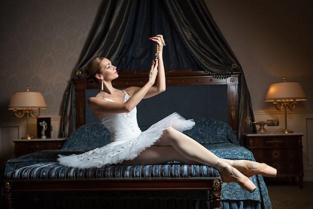 Ballerina in camera da letto e tenendo la collana di perle in interni di lusso