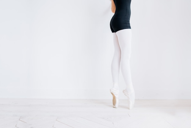 Piedi del ballerino di balletto sul pavimento dello studio. la ballerina adolescente mette le scarpe da punta