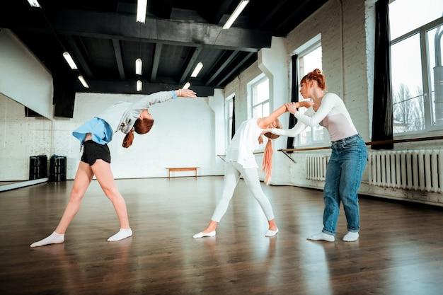 Scuola di balletto. due adolescenti graziosi che sembrano concentrati mentre hanno lezione di ballo nella scuola di balletto