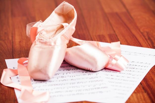 Scarpa da ballo su un pavimento di legno su uno spartito musicale.