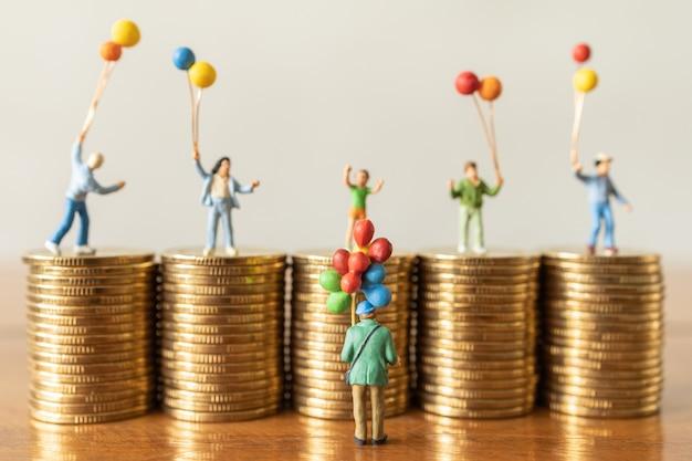 Il venditore di palloncini uomo figure in miniatura persone in piedi con i bambini in cima alla pila di monete
