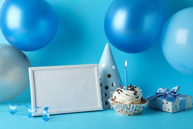Palloncini, cappello compleanno, cupcake, cornice e confezione regalo su sfondo blu, spazio per il testo