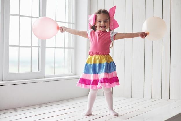Palloncini fuori. bambino in piedi accanto alle finestre nella stanza bianca e in posa per la foto.