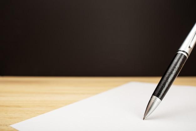Penna a sfera e foglio di carta bianco da vicino. firma, lavoro, apprendimento o concetto di scrittura. copia spazio