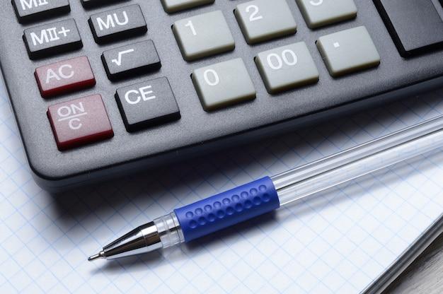 Una penna a sfera e una micro calcolatrice giacciono su un quaderno a quadretti