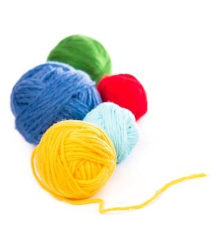 Gomitoli di fili di lana blu, rossi e gialli su fondo bianco