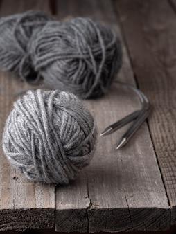 Gomitoli di lana grigia su un tavolo di legno. sullo sfondo dei ferri da maglia. copia spazio.