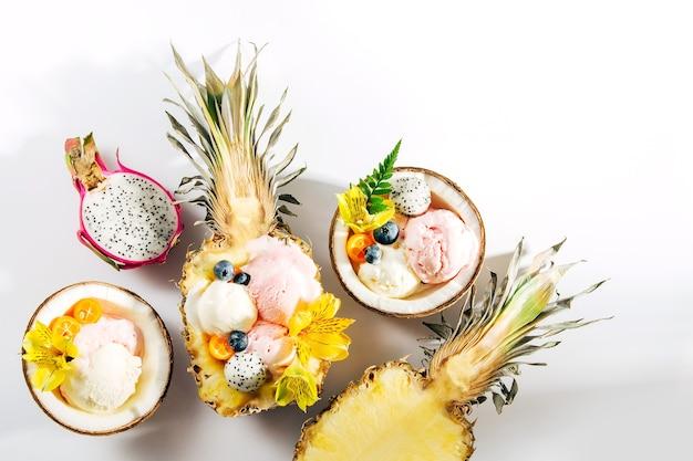 Palline di gelato decorazione fiori e frutti di bosco a metà di cocco e ananas. concetto tropicale estivo.