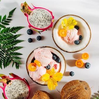 Palline di gelato decorazione fiori e frutti di bosco a metà di cocco con foglie verdi. concetto tropicale estivo.