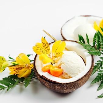Palline di gelato decorazione fiori a metà di cocco. concetto tropicale estivo.