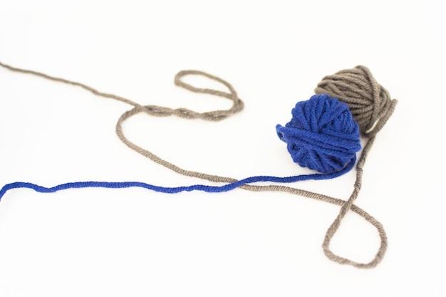 Gomitoli di lana da vicino su sfondo bianco, lana blu e grigia isolato