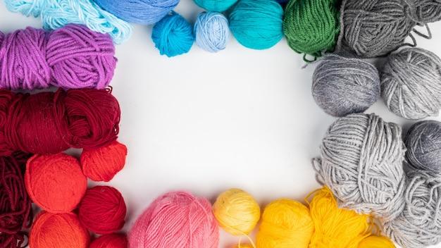 Gomitoli di lana per lavorare a maglia giacciono su una superficie bianca. vista dall'alto. copia spazio.