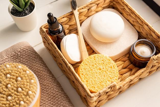 Accessori in bambù per cestino da bagno, saponette, spazzole, spazzolino da denti, asciugamano e olio viso biologico per l'igiene personale.