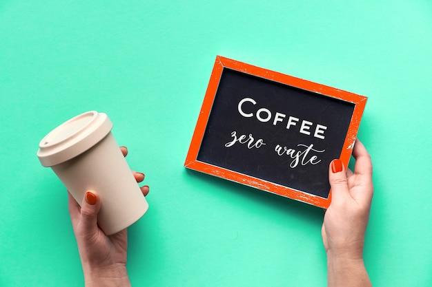 La tazza di caffè di bambù, tiene la tazza o la tazza di viaggio in mano femminile sulla menta verde aqua menthe. piatto, testo