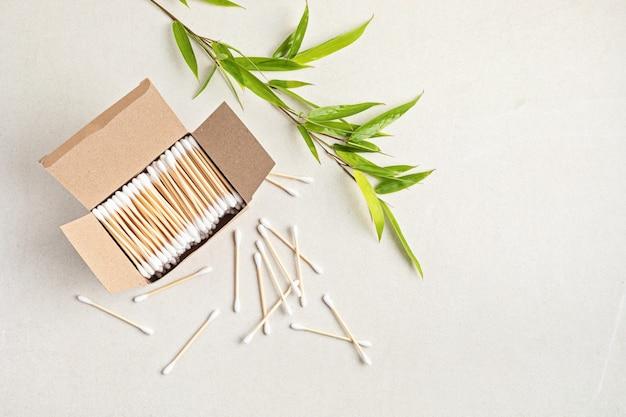 Bastoncini di cotone in bambù in scatola di cartone e ramo di bambù. idea di stile di vita etica, sostenibile, senza plastica. vista dall'alto, mockup