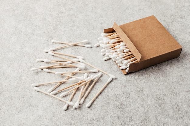 Bastoncini di cotone in bambù in scatola di cartone. idea di stile di vita etica, sostenibile, senza plastica. vista dall'alto, mockup