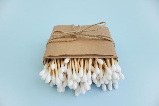Bastoncini di cotone di bambù in scatola di carta sul tavolo blu