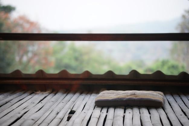 Pavimento in bambù e cuscino in balcone con terrazza sullo sfondo della natura
