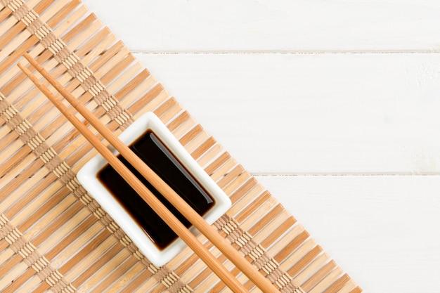Stuoia di bambù e salsa di soia con le bacchette dei sushi sulla tavola di legno bianca