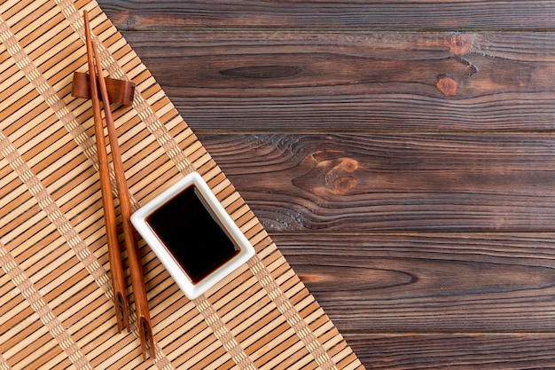 Stuoia di bambù e salsa di soia con le bacchette di sushi sulla tavola di legno. vista dall'alto con sfondo spazio copia per sushi. disposizione piatta.