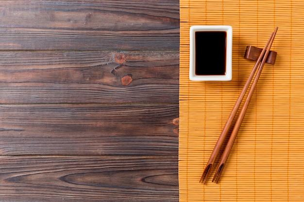 Stuoia di bambù e salsa di soia con bacchette di sushi