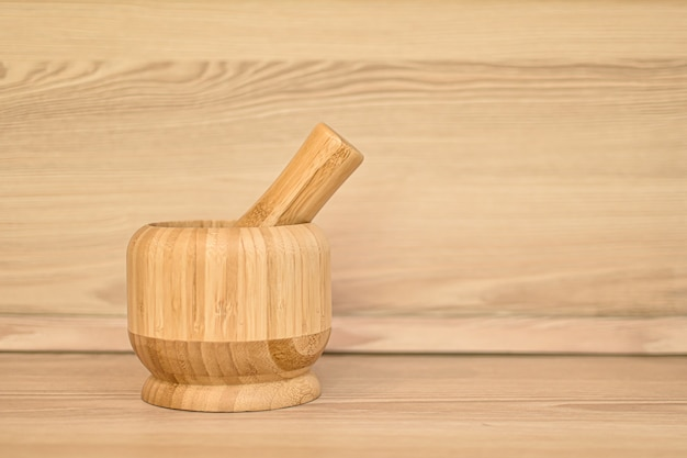 Mortaio di bambù per spezie. interno beige della cucina, mortaio di legno e pestello sul tavolo da cucina