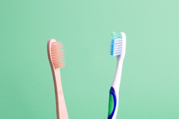 Spazzolini da denti di bambù e plastica su uno sfondo verde concetto di stile di vita zero rifiuti