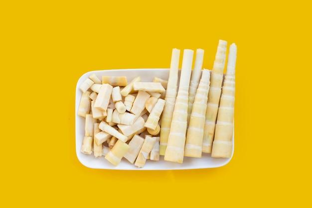 Germogli di bambù in piatto bianco su fondo giallo.