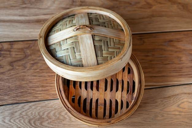 Il vapore di bambù ha messo gli utensili da cucina cinesi sulla vista del piano d'appoggio di legno