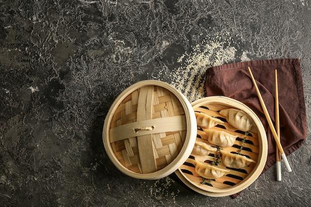 Piroscafo di bambù con gustosi gyoza giapponesi sul tavolo del grunge