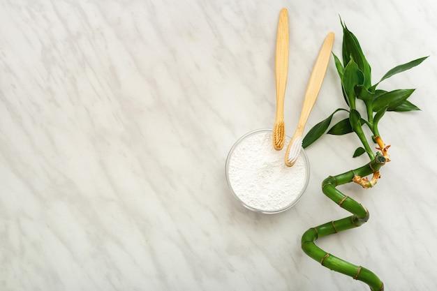 Spazzolino da denti di bambù, polvere di dente di dentifricio pianta di bambù su sfondo bianco marmo