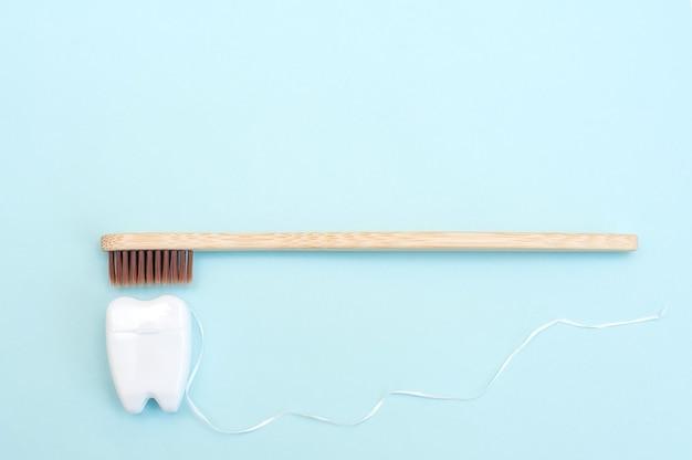 Spazzolino da denti di bambù e filo interdentale bianco a forma di dente bianco su sfondo blu.