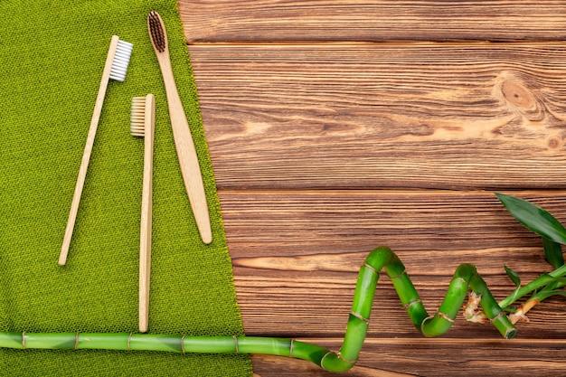 Spazzolini da denti di bambù, pianta di bambù su fondo in legno. spazio copia piatto laico. prodotti da bagno naturali.