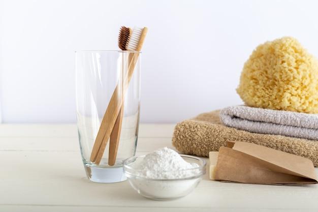 Spazzolini da denti di bambù dentifricio dente in polvere su sfondo bianco. cure odontoiatriche zero sprechi.