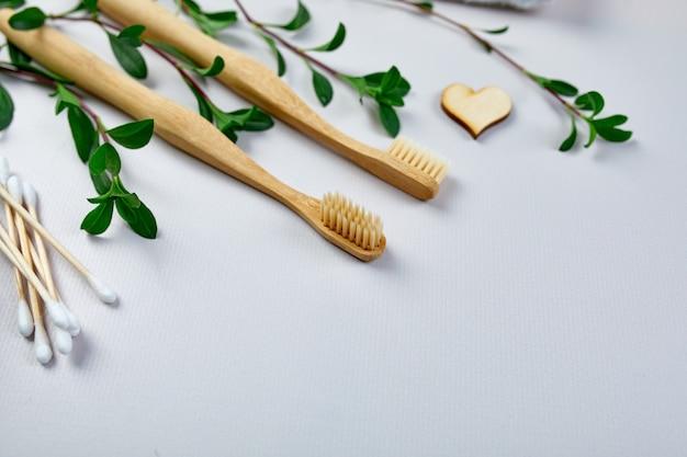 Spazzolini da denti di bambù e bastoncini per le orecchie e foglie verdi su sfondo di carta grigia