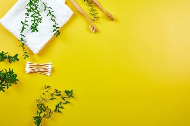 Spazzolini da denti e auricolari in bambù con asciugamano e foglie verdi, prodotti per l'igiene personale ecologici, rifiuti zero, concetto di cura dentale