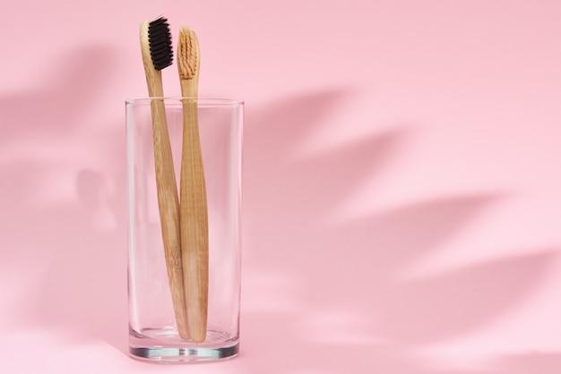 Spazzolini da denti di bambù in vetro e ombre di foglie su sfondo rosa