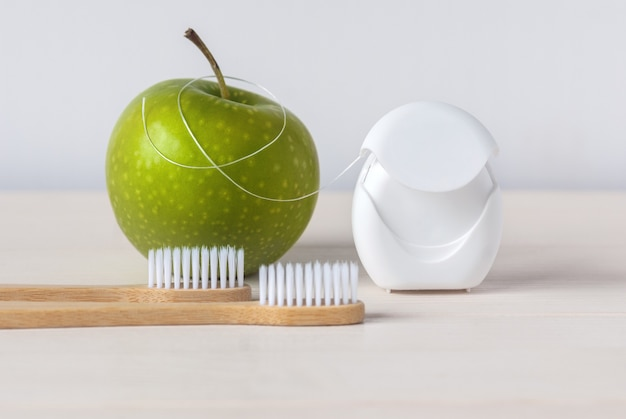 Spazzolini da denti in bambù, mela verde e filo interdentale su sfondo bianco - routine di cure odontoiatriche per mantenere i denti sani