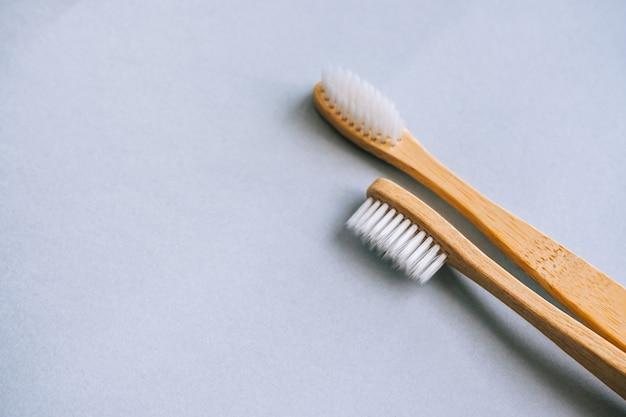 Spazzolini da denti in bambù realizzati con materiali naturali, isolati su sfondo grigio, primo piano.