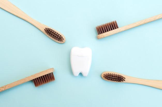 Spazzolini da denti di bambù e un dente bianco su sfondo blu. sfondo