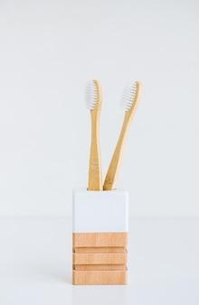 Spazzolini da denti di bambù in una tazza di legno realizzata con materiali naturali, isolati su sfondo bianco