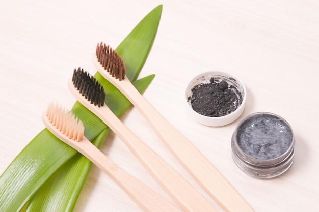 Spazzolini da denti di bambù su una tavola di legno, concetto di stile di vita amichevole di eco del dentifricio in pasta del carbone di legna fatto in casa