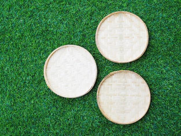 Sopra del cestino di bambù del tessuto su erba verde, priorità bassa per il disegno con lo spazio della copia per testo.