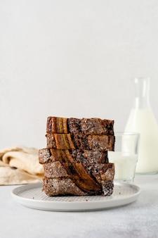 Pane alla banana tagliato a fette in pila con un bicchiere di latte su uno sfondo di cemento grigio chiaro.