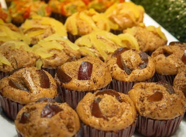 Torta alla banana o muffin alla banana in cupcakes decorano la parte superiore con una varietà di frutta candita pronta da mangiare.