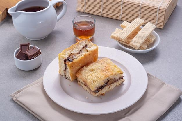 Banana cake lekker servito su un tavolo di cemento con wafer, barrette di cioccolato, miele e tè sul lato