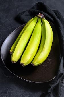 La banana veniva chiamata guineo o bocadillo (musa acuminata). sfondo nero. vista dall'alto. frutta tropicale.