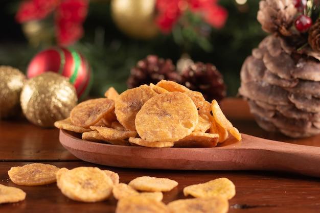 Banana chips nel cucchiaio di legno su uno sfondo di natale
